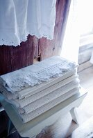 White lace cloths on white wooden stool