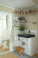 Wooden stool in front of rustic, white-tiled kitchen cooker in corner of room next to doorway showing white wooden bench beyond