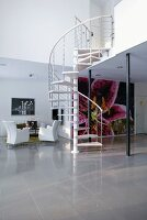 A simple spiral staircase connecting an open-plan living area with a polished stone floor with a gallery