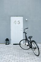 A black bicycle in a paved courtyard in front of a modern house with a unique front door