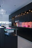 A black fitted kitchen with pink mosaic wall tiles and integrated spot lights