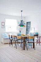 Table and old chairs from a former school and bench with cushions in dining room with white wooden floor