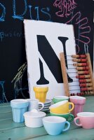 Colourful cups, vintage abacus and board with large letter on surface in front of blackboard