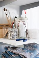 Fabrics, sewing equipment and painting utensils on shelf