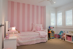 Romantic girl's bedroom in pink and white - vintage bed against striped pink wallpaper