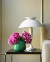 Vase of Pink Peonies on a Side Table with a Lamp