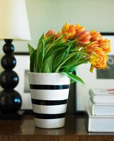 Orange Tulips in a Black and White Striped Vase on a Table