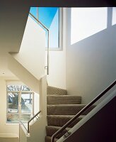Spiral staircase with stair carpet and stainless steel handrails