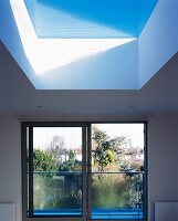 Unframed skylight and wide, floor-to-ceiling sliding window with steel and glass balustrade