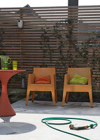 Modern garden chairs and a table in front of a wooden fence on a terrace with a concrete floor