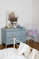 Nostalgic bedroom with pale blue vintage chest of drawers, ornate garden chair and metal bed in foreground