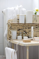 White containers on peeling, vintage metal washstand and towels on radiator