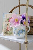 Romantic arrangement on vintage shelving - anemones in floral mug in front of nostalgic postcards