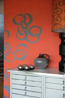 Chest of drawers painted light grey against red wall with retro-style circular pattern