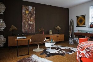 Cow skin rug next to shell chair at desk and dark brown wall in 70s-style room