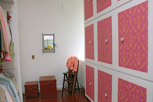Dressing room with fitted wardrobe made from square modules with brightly painted doors