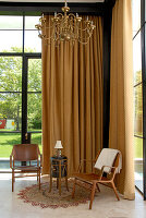 Wooden chairs and side table in front of floor-length, beige curtain in corner of high-ceilinged living room with view of garden