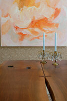 Two candlesticks with blue candles on solid wooden table in front of modern painting on wall