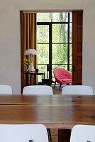 Solid wooden table and chairs with white backs in dining room in front of open doorway showing glass wall with view of garden