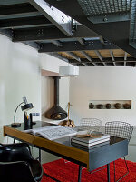 Retro desk with wire-framed chairs in minimalist living area with gallery and exposed steel structure