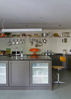 Free-standing kitchen island and tall, retro stool in minimalist dining room