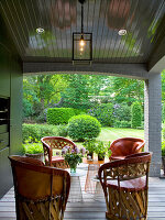 Roofed terrace with Mexican wood and leather chairs and small, designer side tables