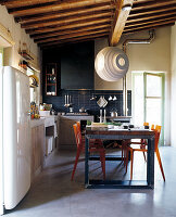 Blue-tiled kitchen with rustic kitchen counter and colourful vintage dining set below modern pendant lamp