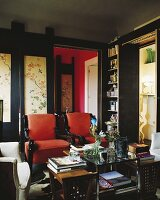 Interior in dark shades with red armchairs and books on table in front of wooden door with Oriental painted motifs