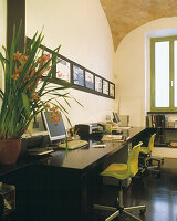 Small architect's studio in stylish Roman loft with brick vaulting; lime green chairs combined with classic black table top and floor