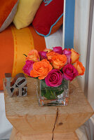 Bouquet of pink and orange roses on designer stool; cushions and bedspread in matching colours in background