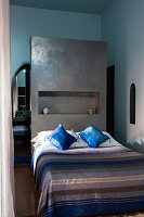 Moroccan bedroom with striped bedspread on bed against grey-painted partition