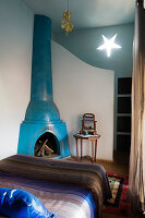 Moroccan bedroom with blue-painted corner fireplace and star-shaped wall lamp