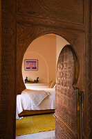 Open, Moroccan-style arched interior door showing view of bedroom beyond