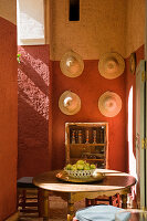 Loggia of Moroccan house with round table in front of straw hats hanging on terracotta wall