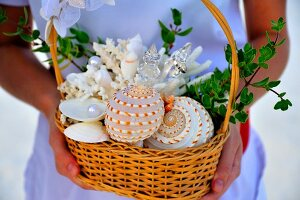 Woman holding basket containing seashells and wedding rings