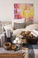 Birds' nests and wooden bowl of decorative items on rustic coffee table in front of black and white sofa and picture of candles and roses