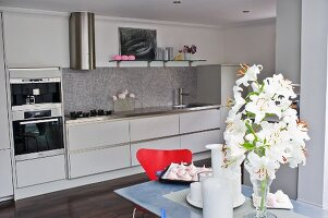 White lilies on dining table in front of white, designer fitted kitchen