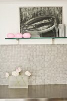 Painting and vases on wall-mounted shelf above mosaic-tiled splashback and stainless steel worksurface in modern kitchen