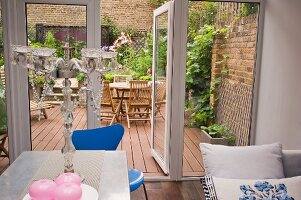 Planted courtyard terrace of town house seen from eclectic kitchen-dining room