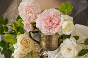 White and pink cut peonies in old brass pitcher