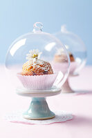 A muffin under a cloche on a mini cake stand on a doily