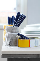 Tin cans wrapped with fabric used as cutlery holders