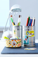 Coloured pencils and paintbrushes in decorated tin cans on a desk
