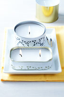 Decorative tin can candles wrapped in decorative white paper