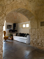 View though stone arched doorway into living room in a Trullo house