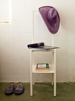 Casual felt hat on back and books on shelf of chair-style valet stand