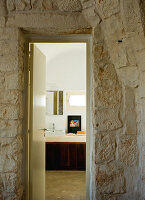 Anteroom with stone wall and view of modern washstand through open bathroom door