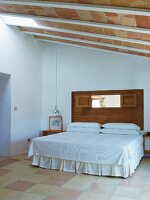 Double bed with valance and white bedspread in simple bedroom with ceiling of roof tiles