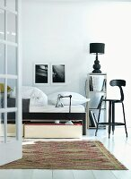 Bed and high, black-painted wooden stool with backrest in minimalist bedroom