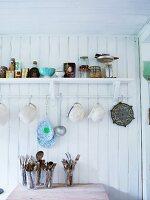 Jugs hanging below shelf on white-painted wooden wall